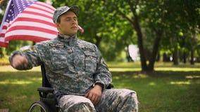 Veterano que saluda, sentándose en silla de ruedas, bandera que agita detrás, Día de la Independencia metrajes