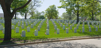 Veterans Cemetery. An expanse of white grave markers accompanied by flags for Memorial Day at a Veteran's Cemetery Royalty Free Stock Images