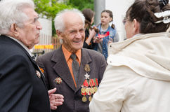 Veterans communicate with passers-by at a gala event Royalty Free Stock Photography