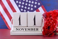 Veterans Day Calendar for November 11. Vintage style wood block calendar for November 11, USA Veterans Day, with Stars and Stripes flag  and red Flanders poppy Stock Photo