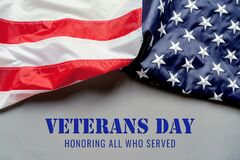 Veterans day. Honoring all who served. American flag on gray background with copy space