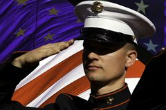 United States Marine Veterans Day Salute, Remember, and Celebrate. A United States Marine soldier renders a salute during the National Anthem at a public royalty free stock photo