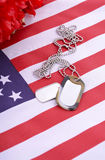 Veterans Day USA Flag with dog tags. And red flanders poppies on rustic red wood background Stock Photos