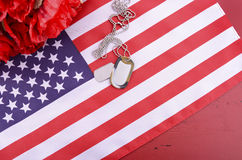 Veterans Day USA Flag with dog tags. And red flanders poppies on rustic red wood background, overhead with copy space Royalty Free Stock Image