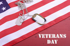 Veterans Day USA Flag with dog tags. On rustic red wood background with sample text stock photography