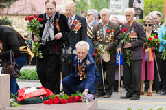 Veterans laying flowers at the monument to fallen soldiers Royalty Free Stock Photo