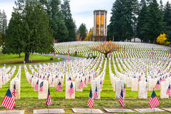 Veterans Memorial  Cemetery with Chimes Tower. SEATTLE - Nov 11: Flags at headstones in Veterans Memorial Cemetery at Evergreen Washelli Memorial Park, the Stock Image