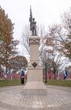 Veterans memorial statue and several red, white and blue American national flags in historic  Park Square Royalty Free Stock Photos