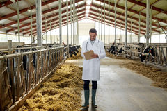Veterinarian with cows in cowshed on dairy farm. Agriculture industry, farming, people and animal husbandry concept - veterinarian or doctor with clipboard and Stock Photo