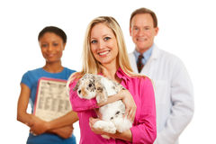 Veterinarian: Customer Holds Rabbit with Vet Behind Stock Photo