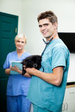 Veterinarian Doctor Carrying A Dog With Female Royalty Free Stock Images