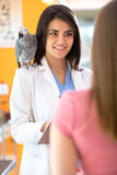 Veterinarian is giving advices to a girl in vet infirmary. Veterinarian is giving advices to a girl with sick parrot in vet infirmary Stock Image