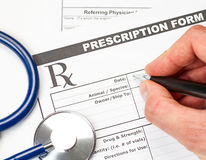 Veterinarian prescription form. Hand with pen over blank vet prescription form with stethoscope and glasses stock images