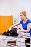 Veterinarian at veteringary clinic examining dog with sore stoma. Veterinarian examining black dog with sore stomach. Young blond woman working at Veterinary royalty free stock image