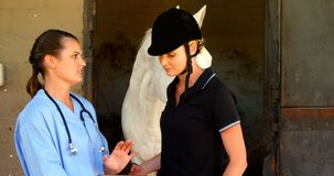Veterinarian and woman interacting while using digital tablet 4k. Veterinarian and woman interacting while using digital tablet in ranch 4k stock footage