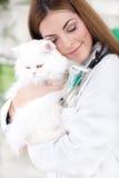 Veterinario con gli occhi chiusi che abbracciano gatto persiano bianco Fotografia Stock Libera da Diritti