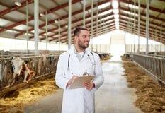 Veterinario con le mucche in stalla sull'azienda lattiera Fotografia Stock Libera da Diritti