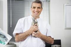 Veterinario de sexo masculino maduro confiado que sostiene el conejo Fotografía de archivo libre de regalías