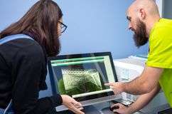 Veterinario que muestra una radiograf?a a un cliente en un ordenador fotografía de archivo libre de regalías