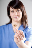 Veterinary with dog biscuit. Veterinarian female shows a dog biscuit Stock Photo
