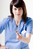 Veterinary with dog biscuit. Veterinarian female shows a dog biscuit, focused on biscuit Royalty Free Stock Photo