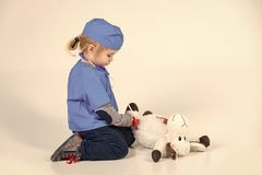 Veterinary services. child in doctor uniform playing vet with toy animal. Veterinary services. child or small boy in blue doctor uniform playing vet with toy stock images