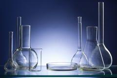 Vetreria per laboratorio vuota assortita, prova-tubi Fondo medico di tono blu Copi lo spazio Fotografia Stock Libera da Diritti