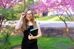 Vetri commoventi del giovane studente femminile in giardino e condizione con i documenti in cartella nera Fotografia Stock Libera da Diritti