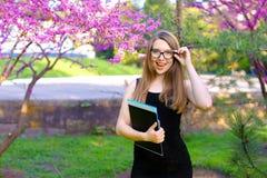 Vetri commoventi della studentessa intelligente in giardino e condizione con i documenti in cartella nera Immagine Stock