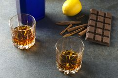 Vetri con brandy, cioccolato, il limone ed altri spuntini sulla tavola grigia alla barra fotografia stock libera da diritti