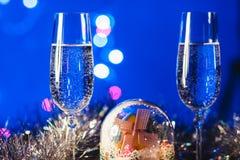 Vetri con champagne contro i fuochi d'artificio e le luci di festa - Ce Fotografie Stock