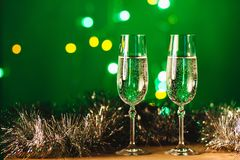 Vetri con champagne contro i fuochi d'artificio e le luci di festa - Ce Immagine Stock Libera da Diritti