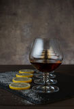 Vetri con il cognac, fette del limone con zucchero su una tavola di legno nei precedenti Immagini Stock