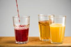 Vetri con il succo di mela, dell'arancia e della ciliegia Immagine Stock Libera da Diritti