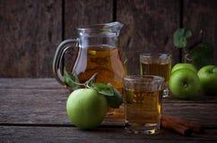 Vetri con il succo di mele sulla tavola di legno Immagini Stock