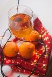 Vetri con le bevande alcoliche, mandarini freschi, bokeh Fotografia Stock