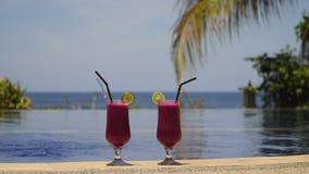 Vetri con un cocktail vicino allo stagno Fotografia Stock