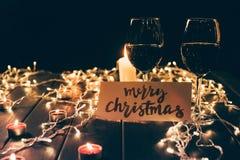 Vetri con vino e la carta di Buon Natale fotografia stock libera da diritti