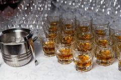 Vetri con whiskey ed il secchiello del ghiaccio sulla tavola del partito Fotografia Stock