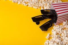 vetri 3D e popcorn su fondo giallo Immagine Stock