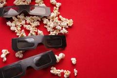 vetri 3D e popcorn su fondo rosso Fotografia Stock