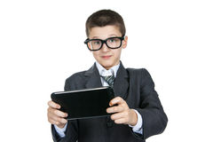 Vetri d'uso colpiti e sorpresi dello scolaro del ragazzo Ragazzo astuto con una compressa in mani Fotografia Stock
