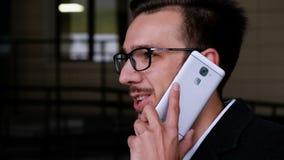 Vetri d'uso del giovane uomo d'affari attraente, risposte una telefonata, parlante sul telefono mentre stando sulla via video d archivio