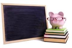 Vetri d'uso del porcellino salvadanaio con la piccola lavagna in bianco, concetto dei soldi di risparmio di istruzione dello stud immagine stock libera da diritti