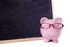 Vetri d'uso del porcellino salvadanaio con la piccola lavagna in bianco, concetto di risparmio dell'istituto universitario Immagini Stock Libere da Diritti