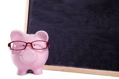 Vetri d'uso del porcellino salvadanaio, lavagna in bianco, isolata, concetto di insegnamento superiore, spazio della copia Immagine Stock