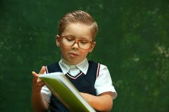 Vetri d'uso del ragazzino che posano con la cancelleria Fotografie Stock Libere da Diritti