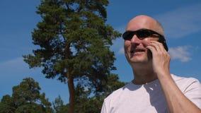 Vetri d'uso dell'uomo calvo che chiamano dal telefono cellulare sul fondo del parco di estate archivi video