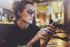 Vetri d'uso della donna affascinante che leggono messaggio di posta elettronica sul telefono cellulare durante il resto in caffet Fotografia Stock Libera da Diritti