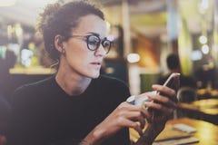 Vetri d'uso della donna affascinante che leggono messaggio di posta elettronica sul telefono cellulare durante il resto in caffet Immagine Stock Libera da Diritti